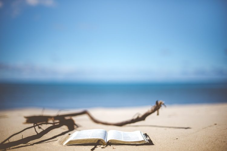 Picture of a Bible on the beach with a beautiful ocean behind it