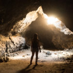 Believing - girl stands looking out of a dark cave toward the light.