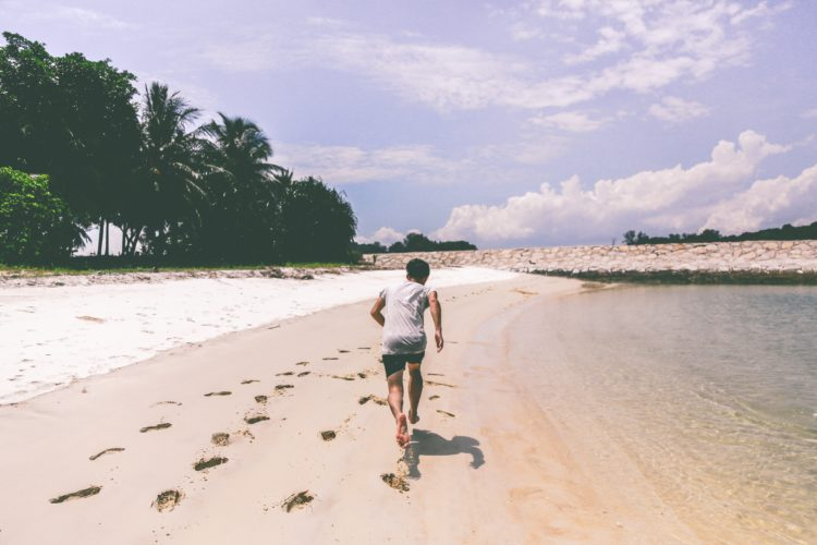 man sprinting parallel to beach; your will is a powerful thing
